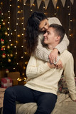 young couple is in christmas lights and decoration, dressed in white, fir tree on dark wooden background, winter holiday concept - 236843136