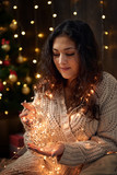 young girl is in christmas lights and decoration, dressed in white, fir tree on dark wooden background, winter holiday concept - 236843154