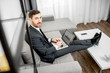Portrait of an elegant businessman dressed in the suit working with laptop on the couch at home or comfortable office