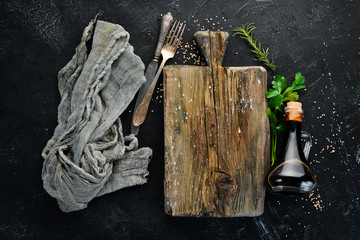 Wooden kitchen board and vegetables. On a black background. Free copy space.