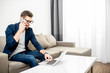 Quadro Businessman dressed casually talking phone during the work with laptop on the couch at home or comfortable office