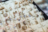 Selective focus on golden earrings with ring on showcase - 236844770