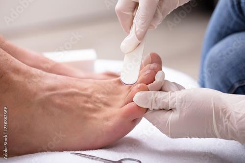 Leinwanddruck Bild Man Undergoing Pedicure Process In Salon