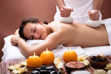 Therapist Giving Massage With Herbal Compress Balls To Woman