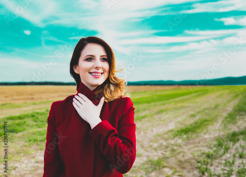 Woman in red coat at countryside field - 236863514