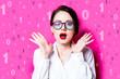 Leinwanddruck Bild - Beautiful redhead businesswoman with one and zero binary code on pink background