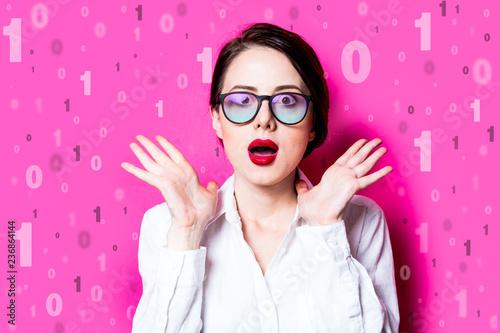 Leinwanddruck Bild Beautiful redhead businesswoman with one and zero binary code on pink background