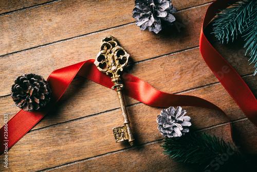 Stary złoty klucz z łękiem i rożkami na drewnianym tle