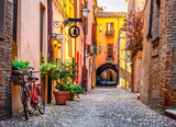 Fototapeta Przestrzenne - Cozy narrow street in Ferrara, Emilia-Romagna, Italy. Ferrara is capital of the Province of Ferrara © ekaterina_belova