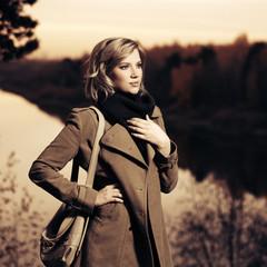 Young fashion woman with handbag walking outdoor