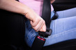Woman Fastening Seat Belt In Car