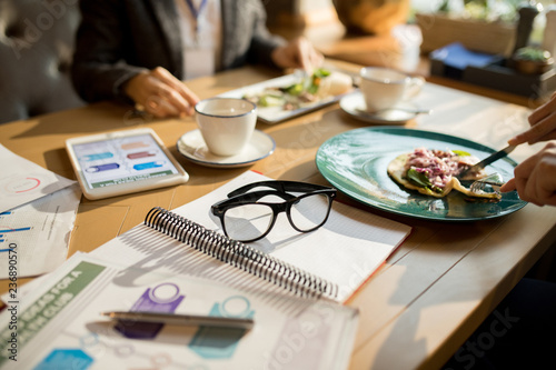 Close-up of unrecognizable women sitting at table with glasses, notepad and marketing charts and eating tasty dinner while taking break during business lunch - 236890570
