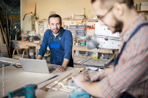 Foto Murales Portrait of mature bearded carpenter talking to apprentice while working in modern joinery, copy space