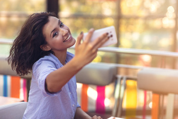 Young woman taking a selfie in coffee shop