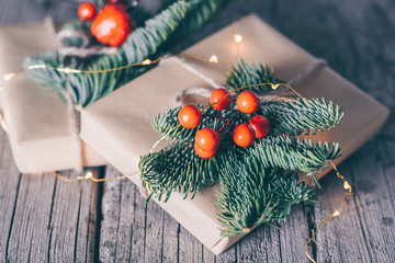 The concept of Christmas presents and winter Holidays. Two Christmas Gift box decorated fir branch and red berry decoration on wooden background. Close-up