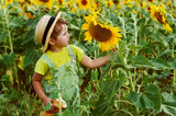 Little girl in a straw hat on a walk in the field with sunflowers