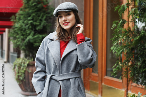fototapeta na ścianę young stylish pretty woman wearing red dress, grey coat and hat posing in the city streets.