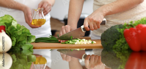 Closeup of human hands cooking in kitchen. Mother and daughter or two female friends cutting vegetables for fresh salad. Friendship, family dinner and lifestyle concepts - 236910777