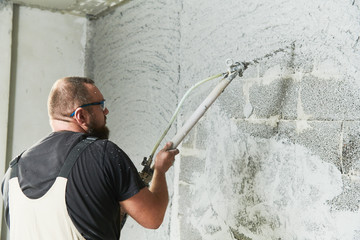 Plasterer using screeder spraying putty plaster mortar on wall
