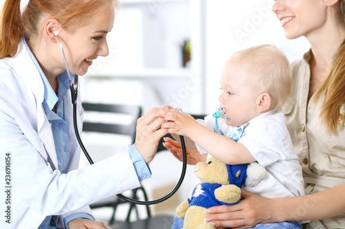 Doktorski egzamininujący chłopiec z stetoskopem. Matka trzyma syna na kolanach. Koncepcja bez matki i medycyny
