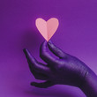 Female hand, showing beauty and skin care symbolism. Holding paper craft pink heart. fashion background, purple neon colors. Minimalism .