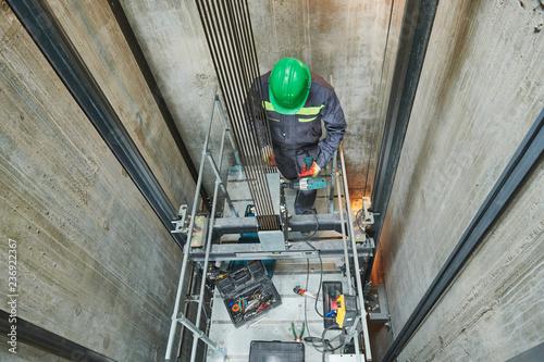 Foto Murales lift machinist repairing elevator in lift shaft