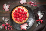Tasty raspberry tart on a black ceramic plate, flat lay on dark wood with red Autumn decorations