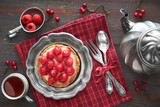 Tasty raspberry tart on a vintaege metal plate with tea pot and cup of tea on red checkered napkin