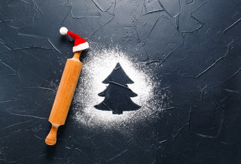 Christmas baking background. Flour in the shape of a Christmas tree on a dark background