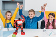 cheerful classmates throwing hands in air after STEM robotics lesson