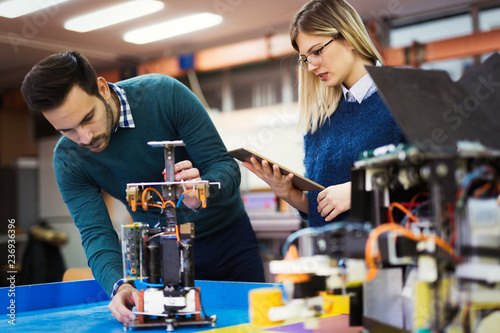 Leinwandbild Motiv Young students of robotics working on project