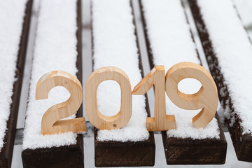 Wooden figures 2019 on the snowy bench. New year and christmas theme