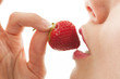 Mädchen isst genussvoll eine Erdbeere