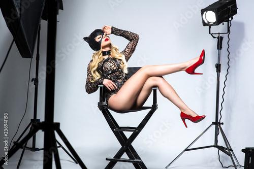 sexy junge dame mit maske sitzt lasziv auf einem Regiestuhl und trägt dabei rote High Heels - 236941198