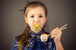 surprised young girl with pacifier in mouth and roll in hands