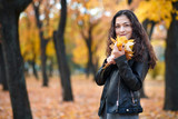 Pretty woman is posing with bunch of maple's leaves in autumn park. Beautiful landscape at fall season. - 236943131