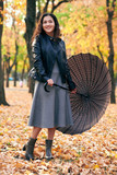 Woman with umbrella posing in autumn park. Bright yellow leaves and trees. - 236943317