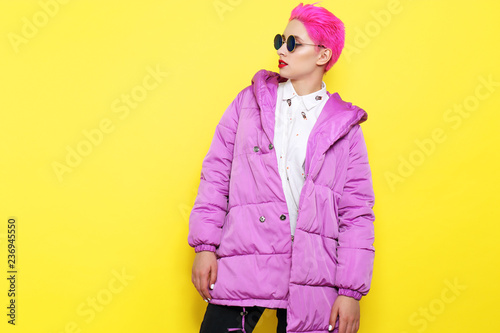 Leinwanddruck Bild Fashion portrait of young hipster woman in lilac down jacket.