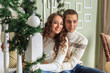 Young man and his girlfriend hug sitting on the steps on the eve of the Christmas holidays
