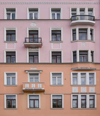 Vintage architecture classical facade apartment building with laconic architectural decorations as meander and medallions. Front view