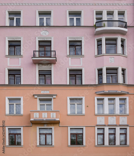 Architektura w stylu vintage klasyczna fasada budynku mieszkalnego z lakonicznymi dekoracjami architektonicznymi jak meander i medaliony. Przedni widok