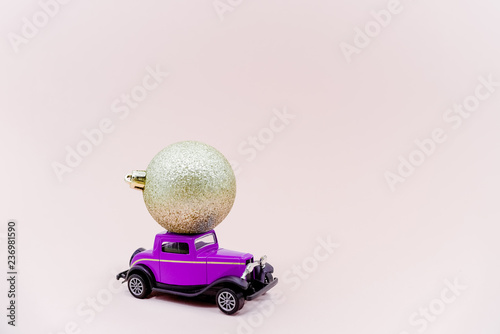 A toy car with christmass ball. Golden ball dark blue car horizontal picture. - 236981590