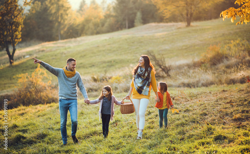 Leinwanddruck Bild A young family with two small children walking in autumn nature.