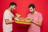 Handsome happy young men friends isolated over red wall background holding big pizza.