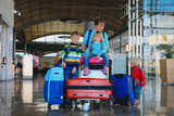 family travel -mother with kids and suitcases in airport