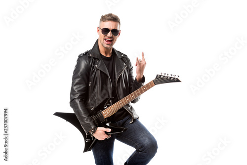 Leinwandbild Motiv excited adult man in leather jacket holding electric guitar and showing rock sign isolated on white