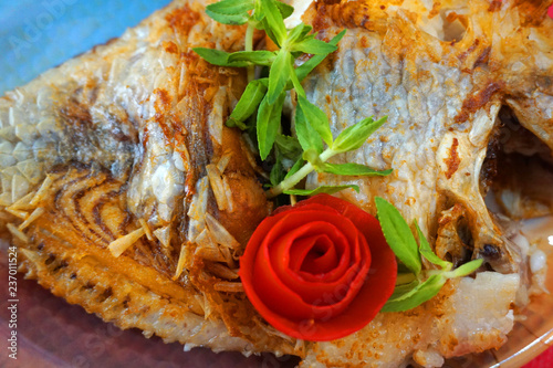 Delicious deep fried fish with mushroom herb chillies dipping sauce in a white bowl and red background - 237011524