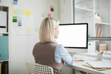 Rear view of busy woman with blond hair sitting at table and working with modern computer while thinking about project in office - 237013522