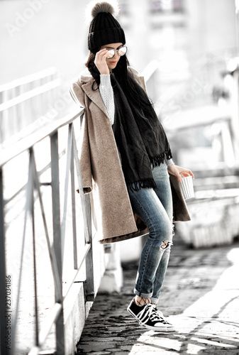 All fashion outfit details. Fashionable woman wearing coat, ripped jeans with sneakers.