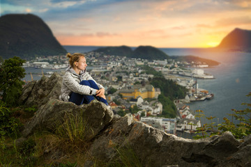 girl in Alesund is sitting alone on a mountain